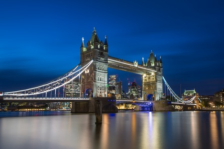 Famous Tower Bridge in the evening with blue sky and reflex on water, London, England Фото со стока