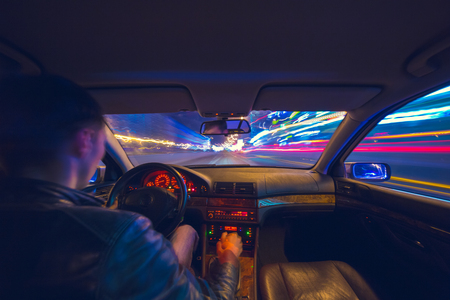 Driver in a car moves at fast speed at the autum night. Blured road with lights with car on high speed.