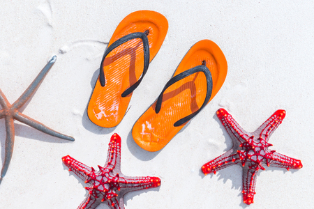 Orange flip flops and starfish on white sandy beach. Summer vacation concept