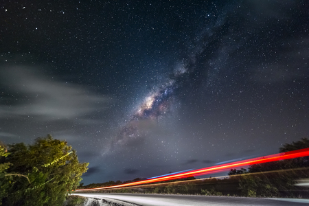 Night sky with milky way and stars. Night road illuminated by car. Light trails Colorful Galaxy