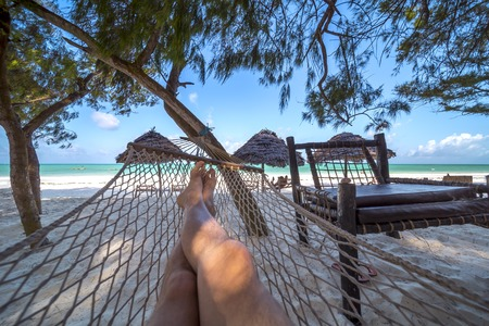 Mans crossed legs in hammock over tropical lagoon 版權商用圖片 - 90140529