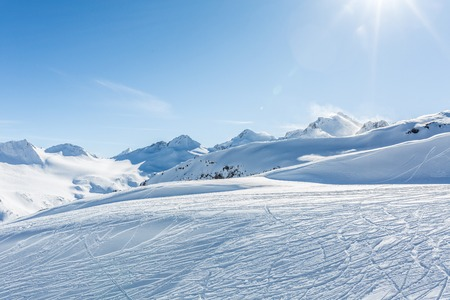 Off-piste ski slope with trace from skis and snowboards at sun winter day. Kavkaz mountains. Reklamní fotografie