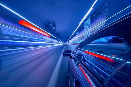 Vista dal lato dell'auto che si muove in una città notturna, strada blusa con le luci con automobile ad alta velocità. Concetto rapido ritmo di una città moderna.