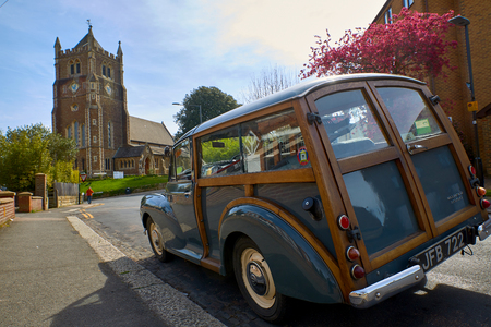 Hastings,England on the 10 April 2017: Christ Church Blacklands and wooden car Morris Minor 1000 parked on street.