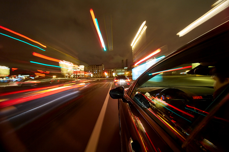 View from Side of Car moving in a night city, Blurred road with lights with car on high speed.