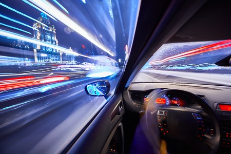 View from Side of Car moving in a night city, Blured road with lights with car on high speed. Concept rapid rhythm of a modern city.