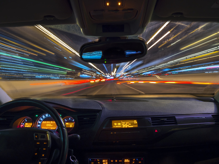 Car driving fast speed at night, view from inside a car