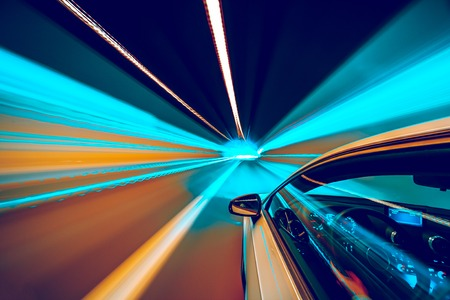 Abstract colors speed motion in urban highway road tunnel, blurred motion toward the central. Shot from side a fast moving car