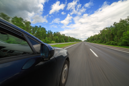 The car moves at high speed on highway at the sunny summer day.