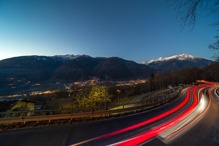 Lightstrails of vehicles in movement for a road in the moonlight Motta, Italy.