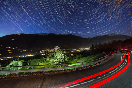 The car and star tails on the sky Motta, Italy. Banco de Imagens