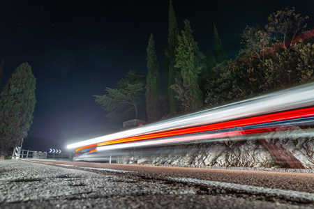 light painting fast cars drive on mountains road, Nago, Italy