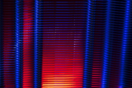 Ribbed metal surface of radiator in dual color light. Heating equipment. Grunge abstract background on the subject of industry, technology or architecture. Banco de Imagens