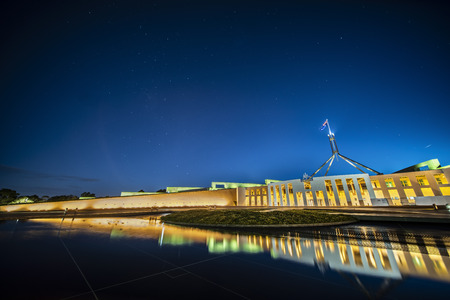 Facade of new parliament house in Canberra on capitol hill at sunset with bright illumination reflecting in blurred waters of pool. Public building free for admission by australians and guests.