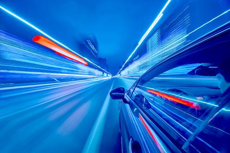 Ansicht von der Seite des Autos bewegend in eine Nachtstadt, Blured-Straße mit Lichtern mit Auto auf hoher Geschwindigkeit. Konzept schneller Rhythmus einer modernen Stadt. Standard-Bild