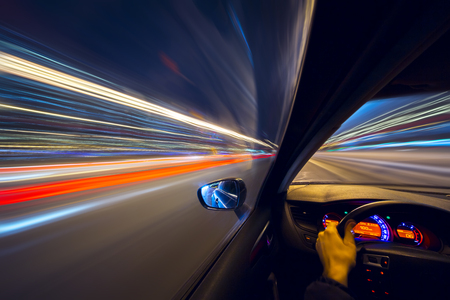 The car moves at high speed at the night. View from driver side.