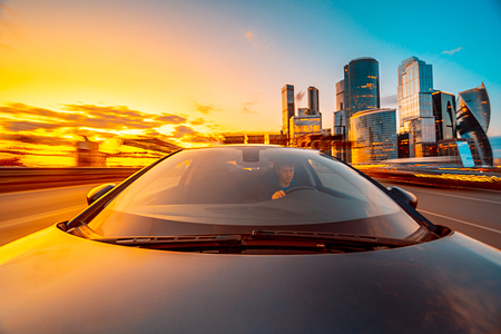 The car moves at high speed at sunset time. Driver in the car and blured road with skyscrapers and sunset sky on bacground. The view from the front to back.