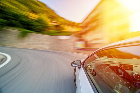 Car in U turn motion blur driving in the Italian mountains