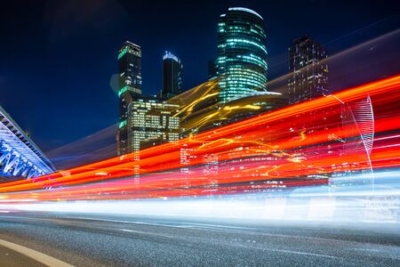 Modern office buildings with light trails of night traffic Imagens
