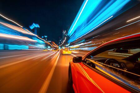 Vista dal lato di una muscle car rossa che si muove in una città notturna, strada blured con luci con auto ad alta velocità. Ritmo rapido di concetto di una città moderna.
