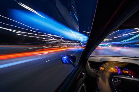 夜の街で移動する車のインターリエから眺め、高速で車でライトを持つ道路をぼかしました。現代都市のコンセプトの急速なリズム。