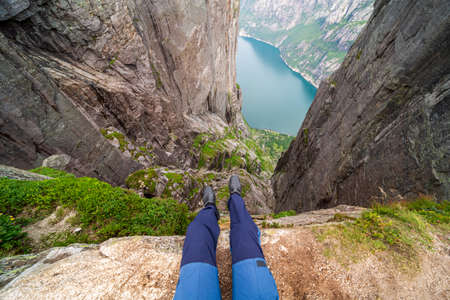 Two feet with hiking boots on them hanging down from a steep cliff with a view on stunning Lysefjorden shimmering with many shades of blue and green. View from Preikestolen. Clear and bright day. Stock Photo