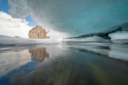 The Baikal Lake in winter with a surface covered with a thick layer of cracked ice. A cliff on Olkhon island with frozen splashes of waves that formed icicles and ice caves - Siberia, Russia