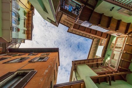 Rovereto, Italy street blue sky in small historic medieval town village in Trento looking up low angle vertical view during sunny summer day multicolored colorful painted walls and balcony