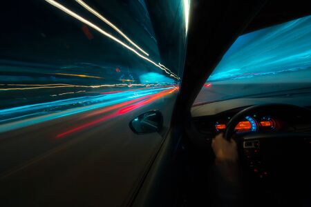 Movement of the car at night at high speed view from the interior with driver hands on wheel. Concept spped of life. Imagens