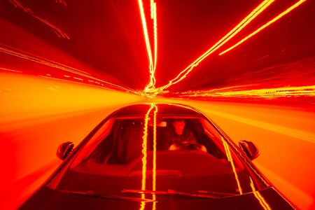 Abstract red color View from Front of Car moving in a night city, Blured road with lights with car on high speed. Фото со стока