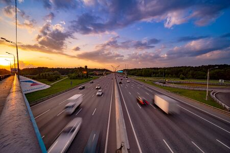 Colourful sunset at motorway with blurry cars . Stock Photo