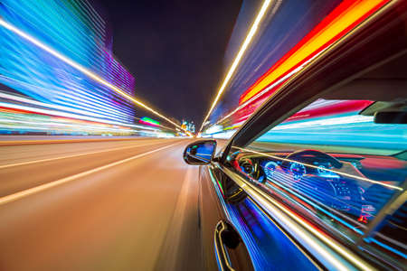 View from Side of a Black Car moving in a night city, Blured road with lights with car on high speed. Concept rapid rhythm of a modern city.