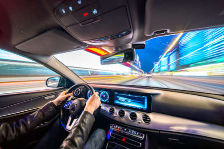 Movement of the car at night at high speed view from the interior with driver hands on wheel. Concept spped of life. Stock Photo