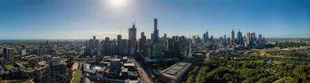 Aerial wide panorama of Melbourne. Modern urban high-rise towers and architecture on CBD waterfront.
