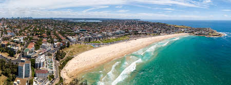 Wide aerial panorama of Sydney Eastern Suburbs facing open sea of Pacific ocean with vista of famous Bondi Beach. City CBD towers on horizon.