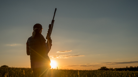Silhouette of woman hunter. It stands in a picturesque place with a gun at sunset. Sports shooting and hunting concept Stock Photo