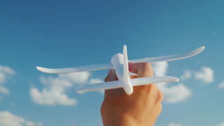 A male hand holds a toy airplane directed to the sky. Idea and dream in business concept