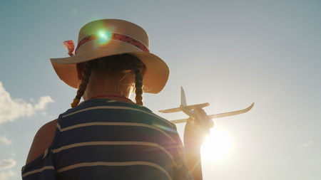 Cute child plays with a toy gun. In the rays of the sun, the rear view. Baby dreams concept