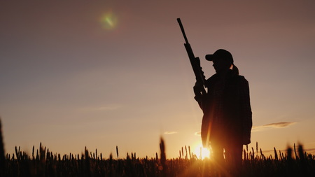 Silhouette of a woman with a gun in her hands. Hunter in the field at sunset
