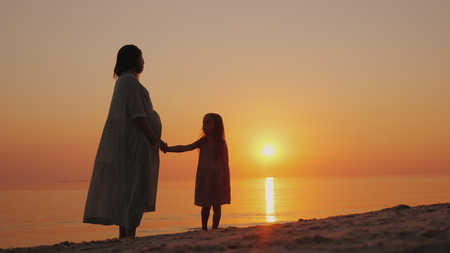 Silhouette of a pregnant woman with a baby near by. Stand near the sea at sunset. Waiting for the second change.
