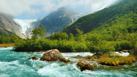 Briksdal glacier with a mountain river in the foreground. The amazing nature of Norway