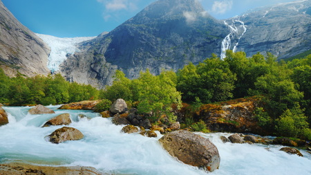 The incredible nature of Norway is a turbulent river from the melted waters of the Briksdal Glacier Foto de archivo