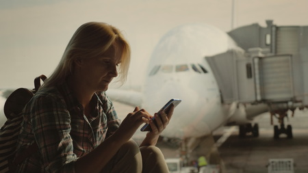 Woman traveler uses a smartphone in the airport terminal on the background of a large airliner outside the window
