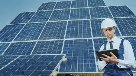 A young businessman in a white helmet uses a tablet on the background of solar panels