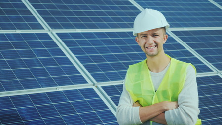 Portrait of a worker in overalls and a helmet on the background of solar panels. Smiles, looks into the camera Standard-Bild