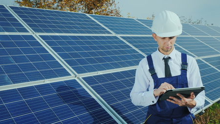 An engineer in a helmet and overalls uses a tablet on the background of a solar power station