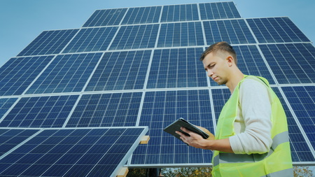 A worker uses a tablet in a large ground-based solar panel. Alternative energy