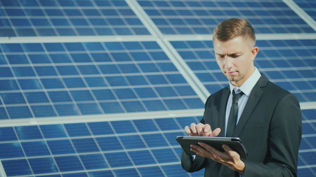 A young businessman uses a tablet near a solar power station