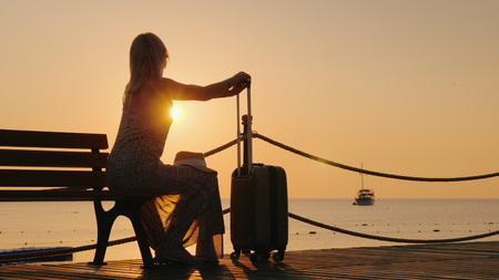 An adult woman sits in a summer sarafan on the beach, sits on a bench and holds onto a suitcase on wheels early in the morning