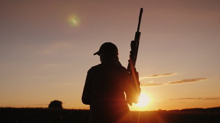 Back view: A woman with a gun goes across the field. The beginning of the hunting season.